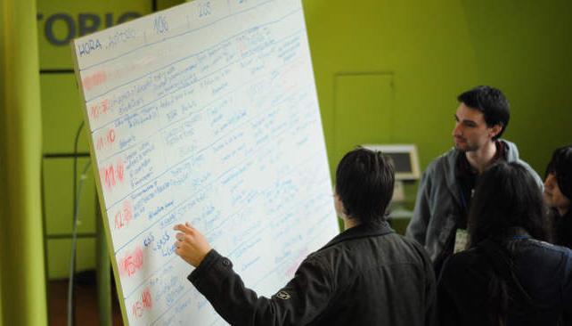 Los asistentes echan un vistazo a la pizarra donde se anotan las diversas charlas del Barcamp (foto: gentileza Luciana Macagno Grifasi).